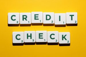 credit check spelled out on green and white scrabble tokens