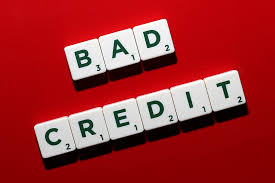 bad credit spelled out in black letters on white scrabble tokens sitting on a dark red background