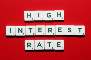 high interest rate spelled out on green and whit scrabble tokens lying on a yellow background