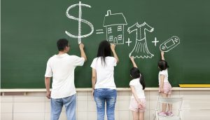Family in front of blackboard drawing a $ sign for savings and that it equals house, nice clothes and swimming pool